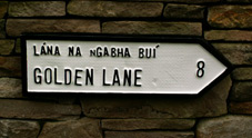 Golden lane road sign with Iirish